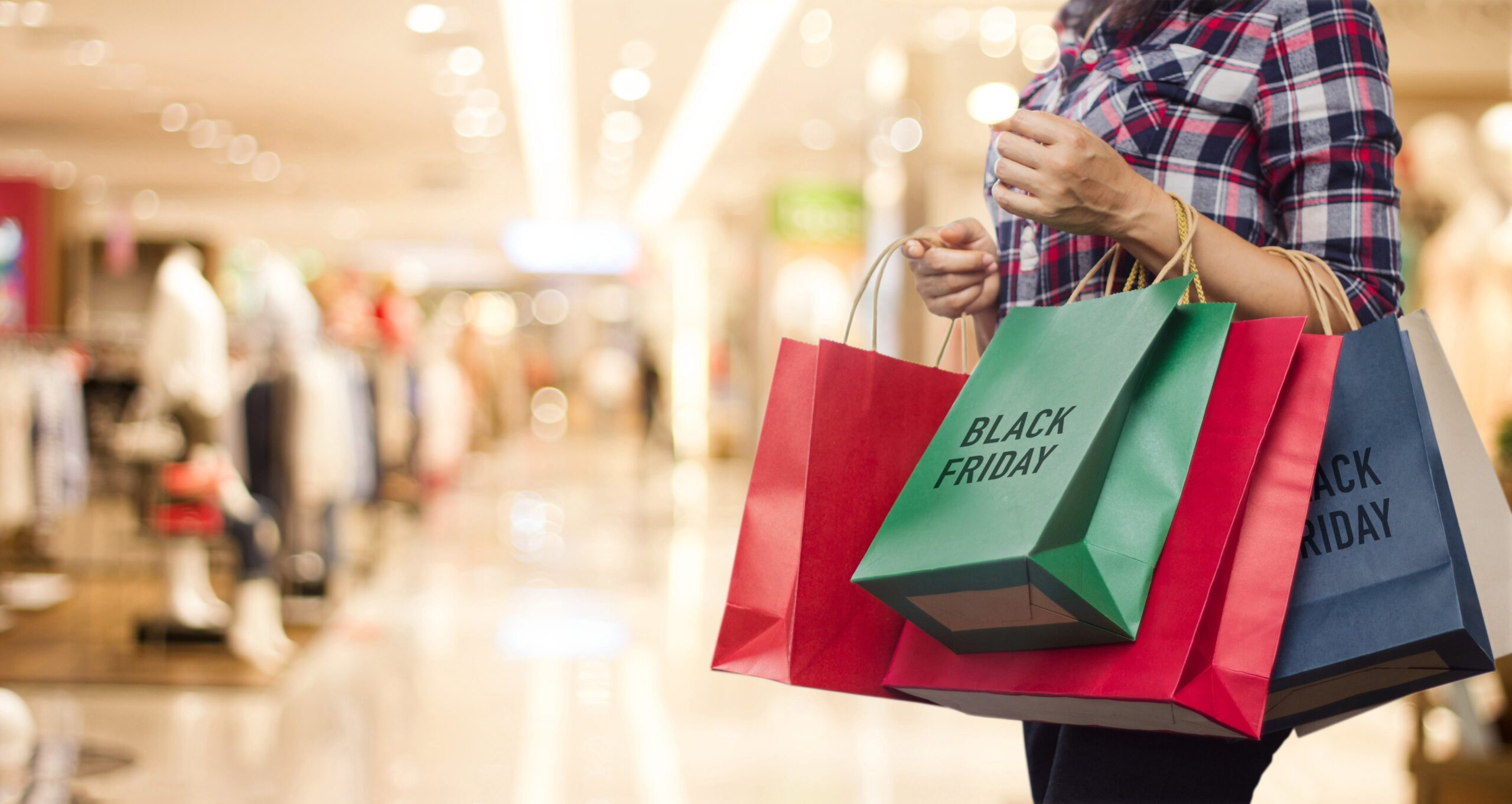 black friday woman holding many shopping bags while walking in the shopping mall min scaled